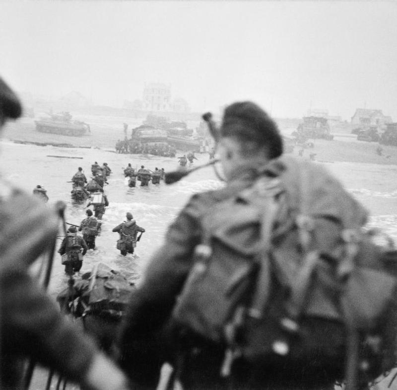 Lord Lovat leading his troop ashore at Sword Beach.   Bill Millin is in the foreground waiting to follow.